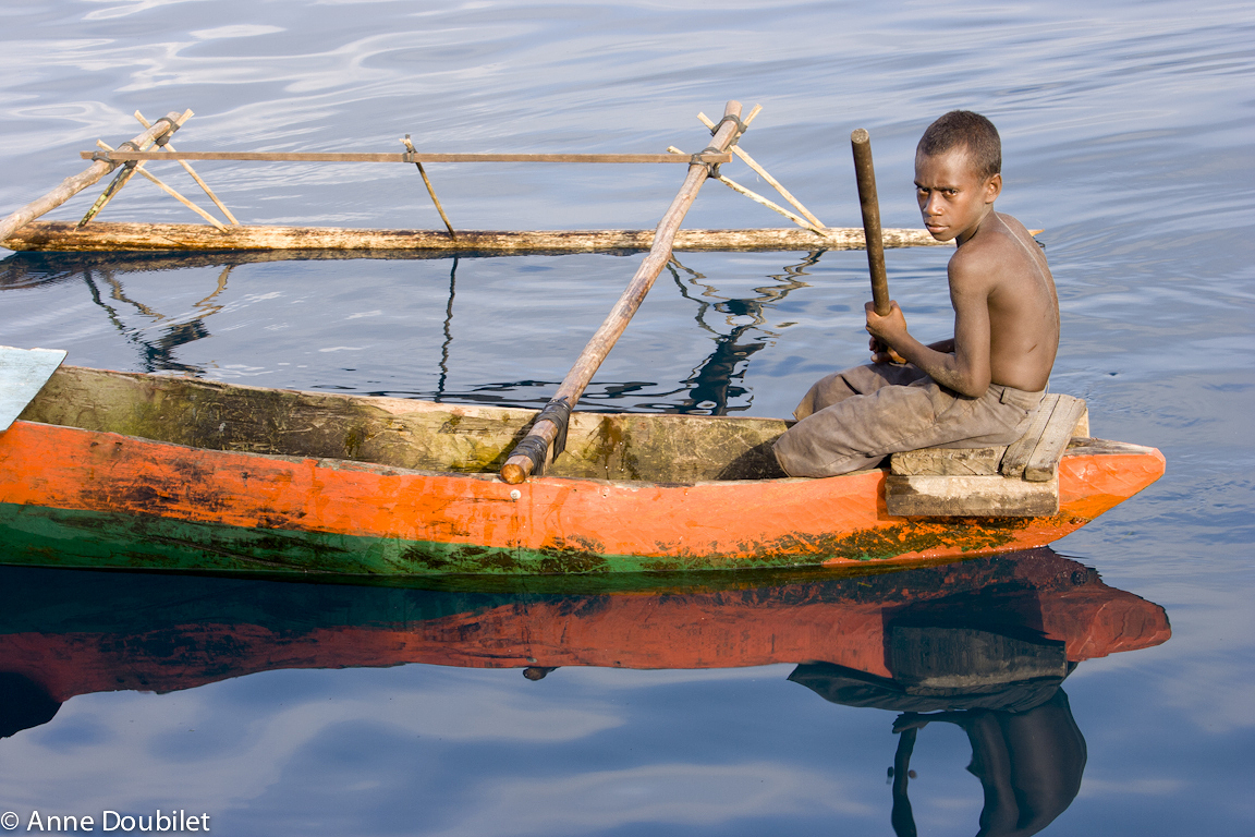 Boy in orange canoe, Papua New Guinea.